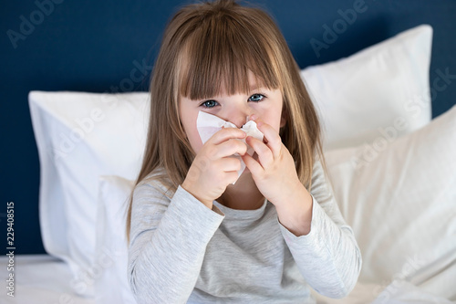 Fotografia cold sick child laying on bed and blowing her nose in tissue