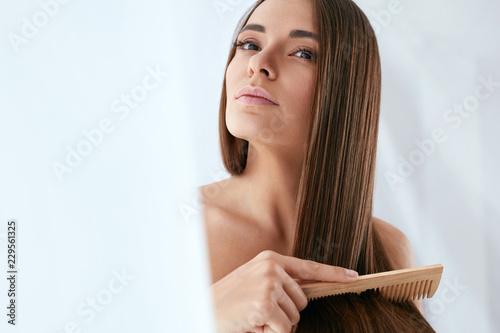 Fototapeta premium Pielęgnacja włosów uroda. Piękna kobieta czesanie długie naturalne włosy