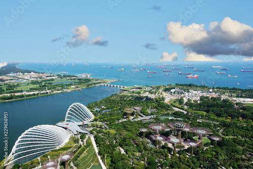 Fototapeta premium Port w Singapurze z wieloma łodziami transportowymi i ogrodami nad zatoką, widok z lotu ptaka z hotelu Marina Bay Sand w słoneczny dzień, Singapur, 15 października 2018 r.