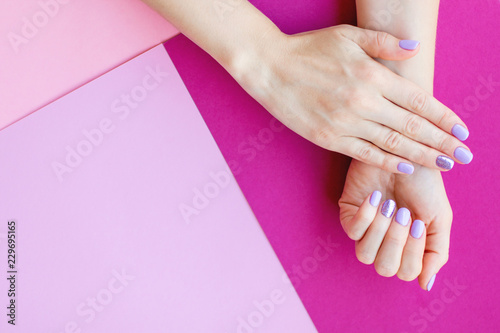 Stylish trendy female manicure. Beautiful young woman's hands on pink, violet background with copyspace. Flat lay style. Manicure concept.