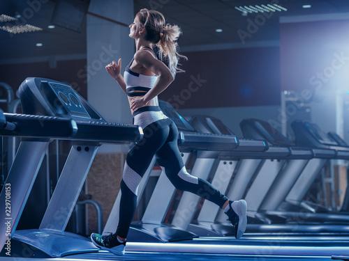 Fotografia Woman trains on a treadmill in the gym