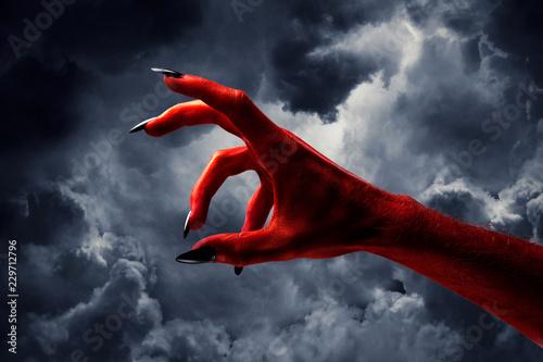 Halloween red devil monster hand with black fingernails against a dark sky Fototapet