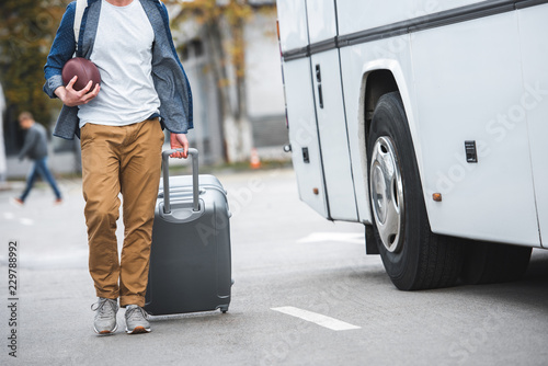 partial view of man with rugby ball carrying bag on wheels near travel bus at street