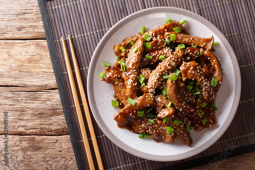 Traditional Asian beef teriyaki with green onions and sesame close-up on a plate. Horizontal top view