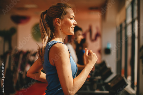 Young woman warming up on treadmill at gym Fototapeta