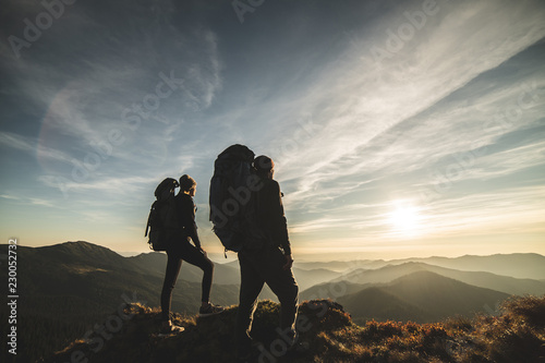 Платно The couple standing on a mountain with a picturesque sunset background