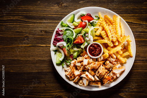 Kebab - grilled meat with french fries and vegetables on wooden background