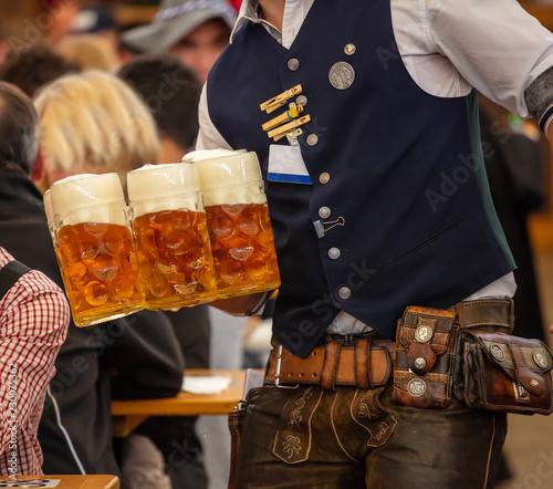 Fényképezés Oktoberfest, Munich, Germany. Waiter serving beers, closeup view