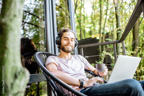 Stampa su Tela Poortrait of a handsome man working with laptop and headphones on the balcony of