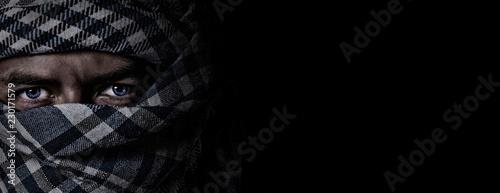 Slika na platnu an arab face in a scarf keffiyeh on a black background