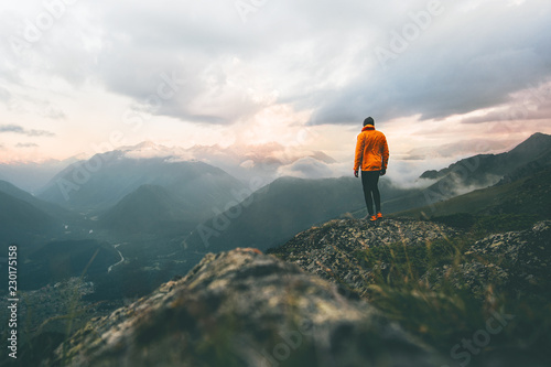 Fototapeta Man adventurer on mountain summit hiking Traveling alone heathy lifestyle active