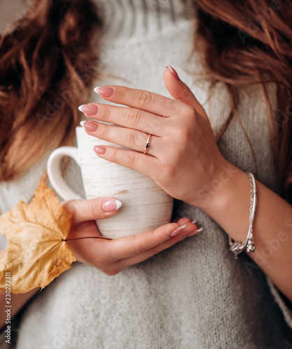 Woman hands holding  cup of coffee or black tea .Close up on hot beverage in girl hands.Warming break on autumn day.