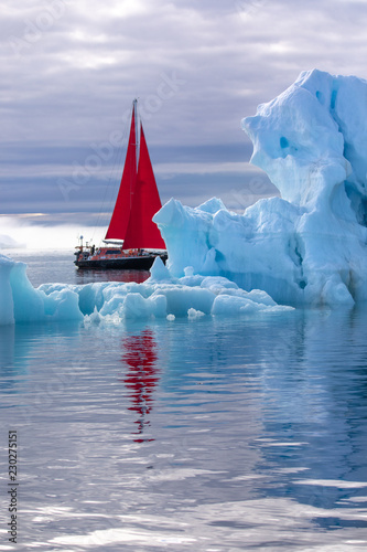 Beautiful red sailboat in the arctic next to a massive iceberg showing the scale. Ilulissat, Disko Bay, Greenland.