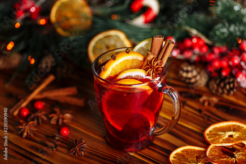 Canvas Print Christmas mulled red wine with spices and fruits on a wooden rustic table