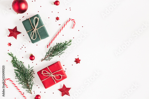 Christmas composition. Gifts, fir tree branches, red decorations on white background. Christmas, winter, new year concept. Flat lay, top view, copy space