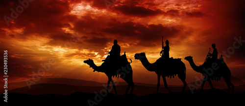 Obraz na płótnie Three kings - traveling in the desert against the background of red clouds risin