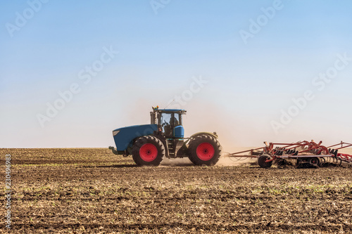 Canvas Print Agricultural tractor is working in the field under blue sky at daylight