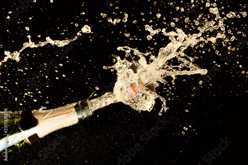 Wallpaper Mural Celebration theme with explosion of splashing champagne sparkling wine on black background