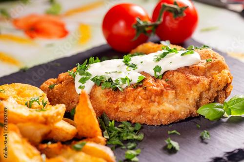 Obraz na plátně Pork schintzel with a white sauce, fries and herbs