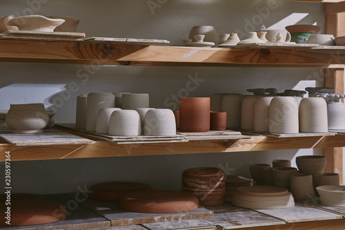 Fényképezés ceramic bowls and dishes on wooden shelves at pottery studio