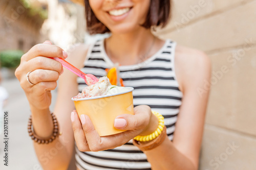 Traveler woman is trying ice cream wearing a straw hat in the city