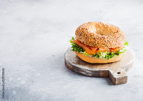 Fresh healthy bagel sandwich with salmon, ricotta and lettuce on vintage chopping board on stone kitchen table background. Healthy diet food. Space for text