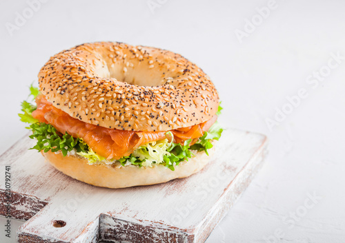 Fresh healthy bagel sandwich with salmon, ricotta and lettuce on vintage chopping board on stone kitchen table background. Healthy diet food