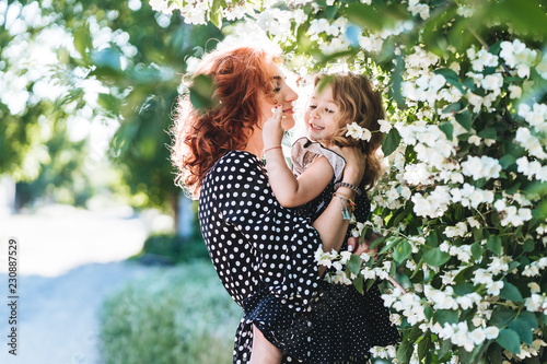Fotografia Young woman stands near jasmine with a small daughter