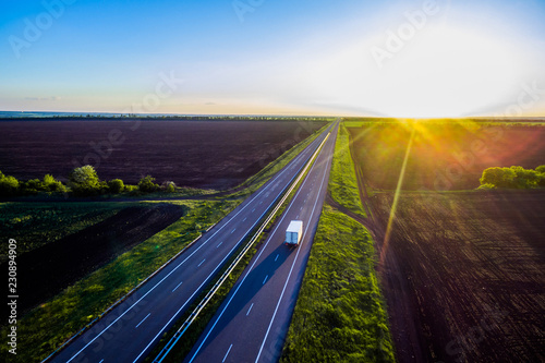 White trailer car driving on asphalt road On the sunset . Road seen from the air. Aerial view landscape. dron  photography.