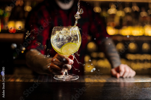 Bartender making splash of a delicious Gin Tonic cocktail with lime slices
