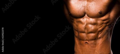 Canvas Print Muscular shape male torso on black background.