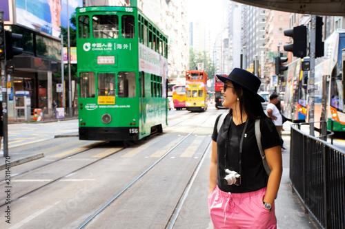 Fototapeta premium Tajska kobieta idzie na dworzec autobusowy na wycieczkę tramwajem retro i vintage w Hongkongu w Chinach