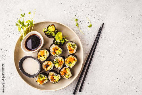 Vegan sushi rolls with pumpkin, brown rice and avocado, top view.