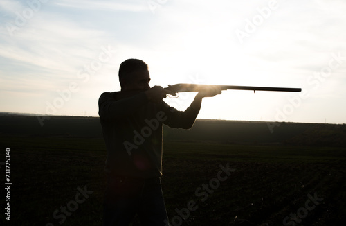 Obraz na płótnie silhouette of hunter with old double barreled shotgun wich hunting and taking ai