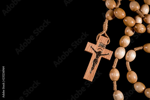 Fototapeta A brown rosary lying on a black background