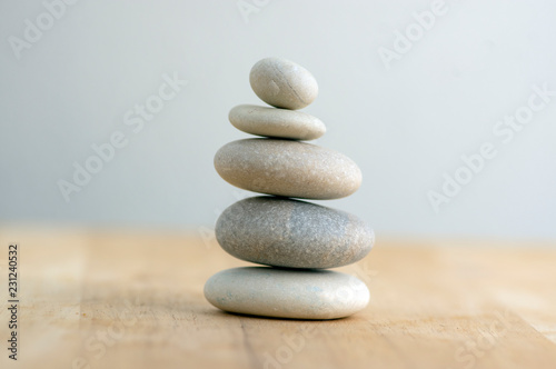 Leinwand Poster Stone cairn on striped grey white background, five stones tower, simple poise st