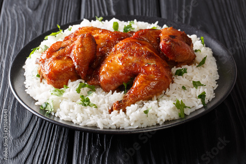 Half chicken baked in garlic, soy, ginger and honey sauce served with rice on a plate close-up on a black table. horizontal