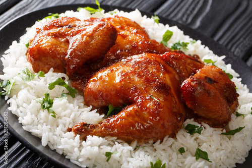 Indonesian main course baked chicken in garlic, soy, ginger and honey sauce served with rice on a plate close-up. horizontal