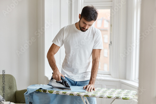 Obraz na plátne Hard working bearded man dressed in white t shirt, irons shirt on ironing board, takes care of clothes, does household duties, poses against window background