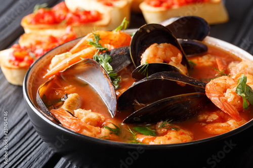 Freshly cooked seafood bouillabaisse soup with shrimps, fish fillets and mussels closeup in a bowl. horizontal