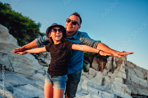 Obraz na plátně Father and daughter standing on rock at beach