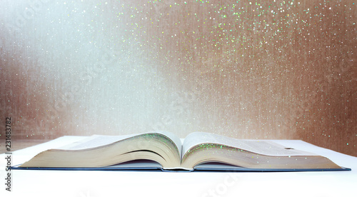 light from a magical book with reflections and green lights against an old and shabby wall