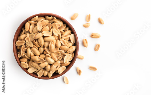 Roasted salted peanuts in wooden bowl on white background,top view