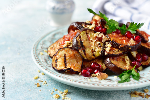 Grilled eggplants in tomato sauce with walnuts and pomegranate seeds.