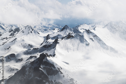 Panoramic view of high mountain peaks in snowy and foggy cold weather Fototapeta