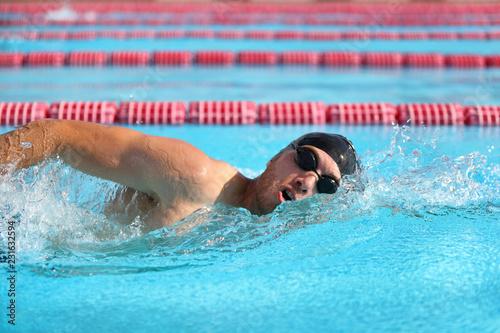 Swimmer man athlete swimming in pool lanes doing a crawl lap. Swim race freestyle.