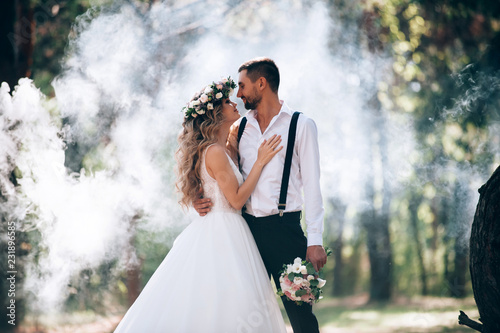 bride and groom on the background of fairy fog in the forest Fototapete