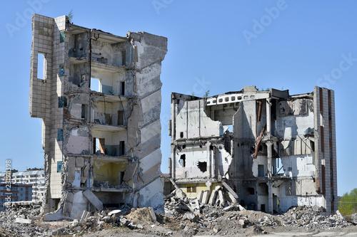 Fotografia A pile of concrete debris on the background of a large destroyed building