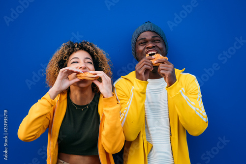 Young couple eating burger outdoors
