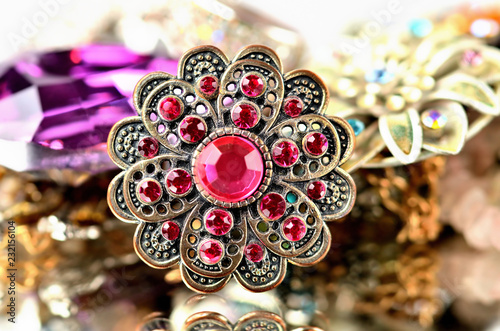 Close-up of richly decorated brooch - red artificial stones Fotobehang